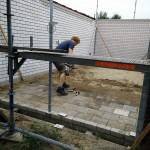 Rob maakt de vloer van de garage van oude stoeptegels